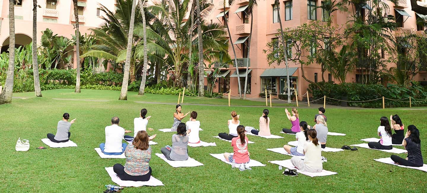 a group of people doing yoga on a beautiful lawn in Hawaii