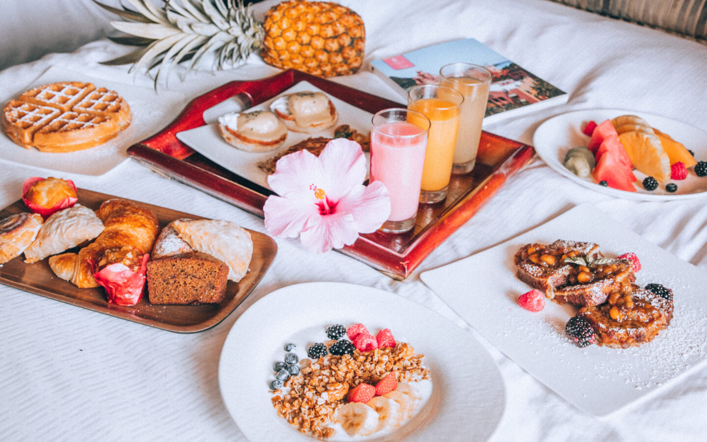 pastries on tray near cereals on plate and juice on another tray beside pineapple fruit
