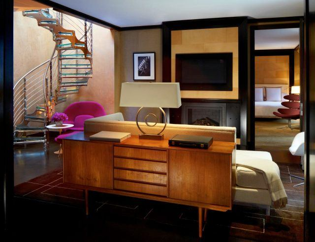 Suite living room with cabinet, couch, TV, fireplace and spiral staircase