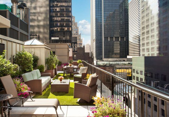 Rooftop deck with seating, umbrellas, and plants