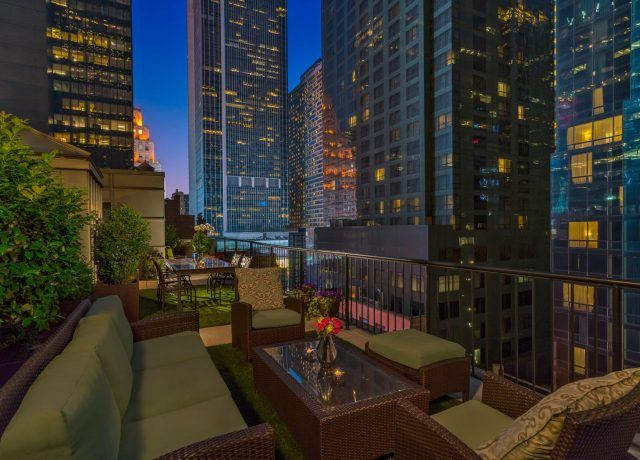 Rooftop Terrace at night with seating and city in the background