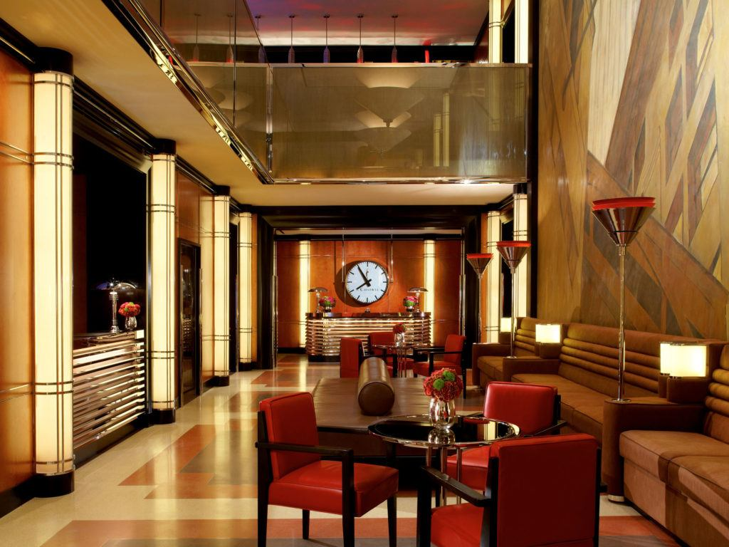 A large clock over a desk at the end of a long lobby with lots of dark tones