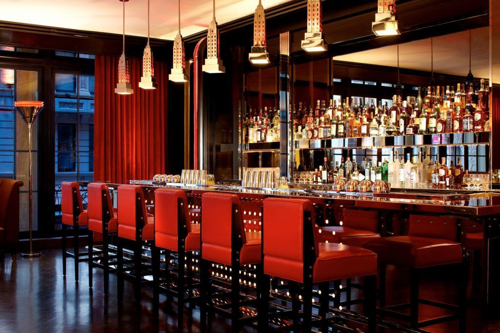 A dark richly colored bar with 6 red chairs and many bottles of liquor