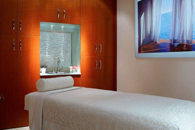 A single massage bed in a spa treatment room with a sink set into a wall of wooden cabinets