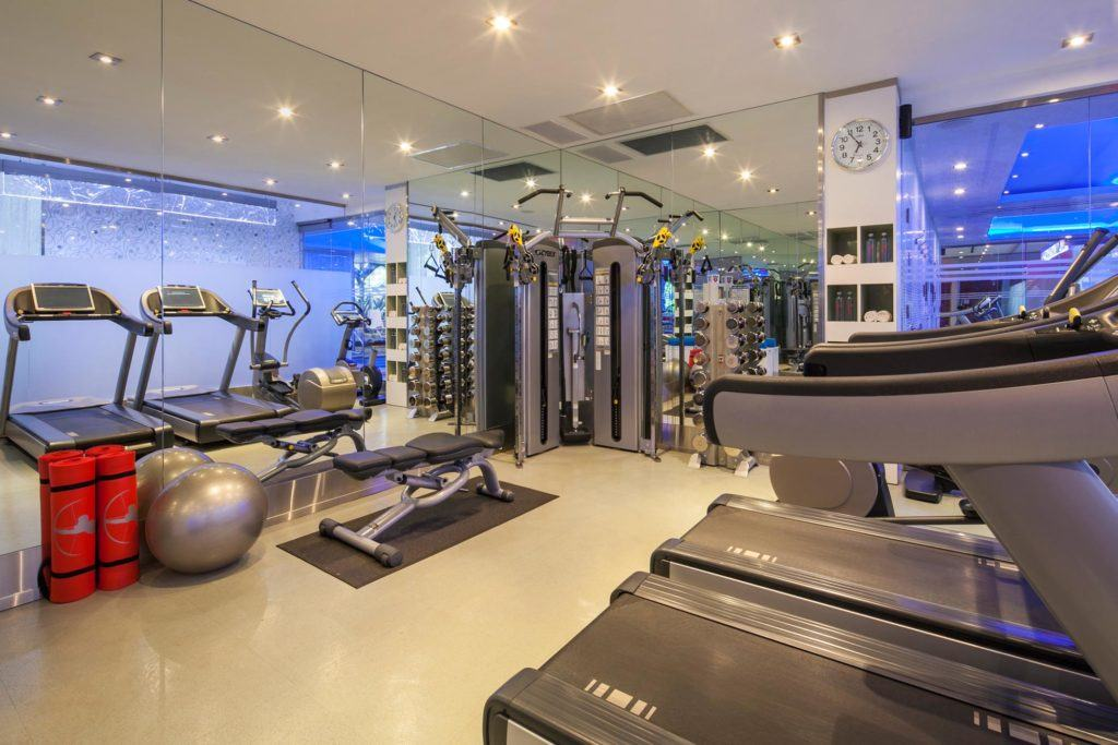 Room with exercise equipment and mirrored walls