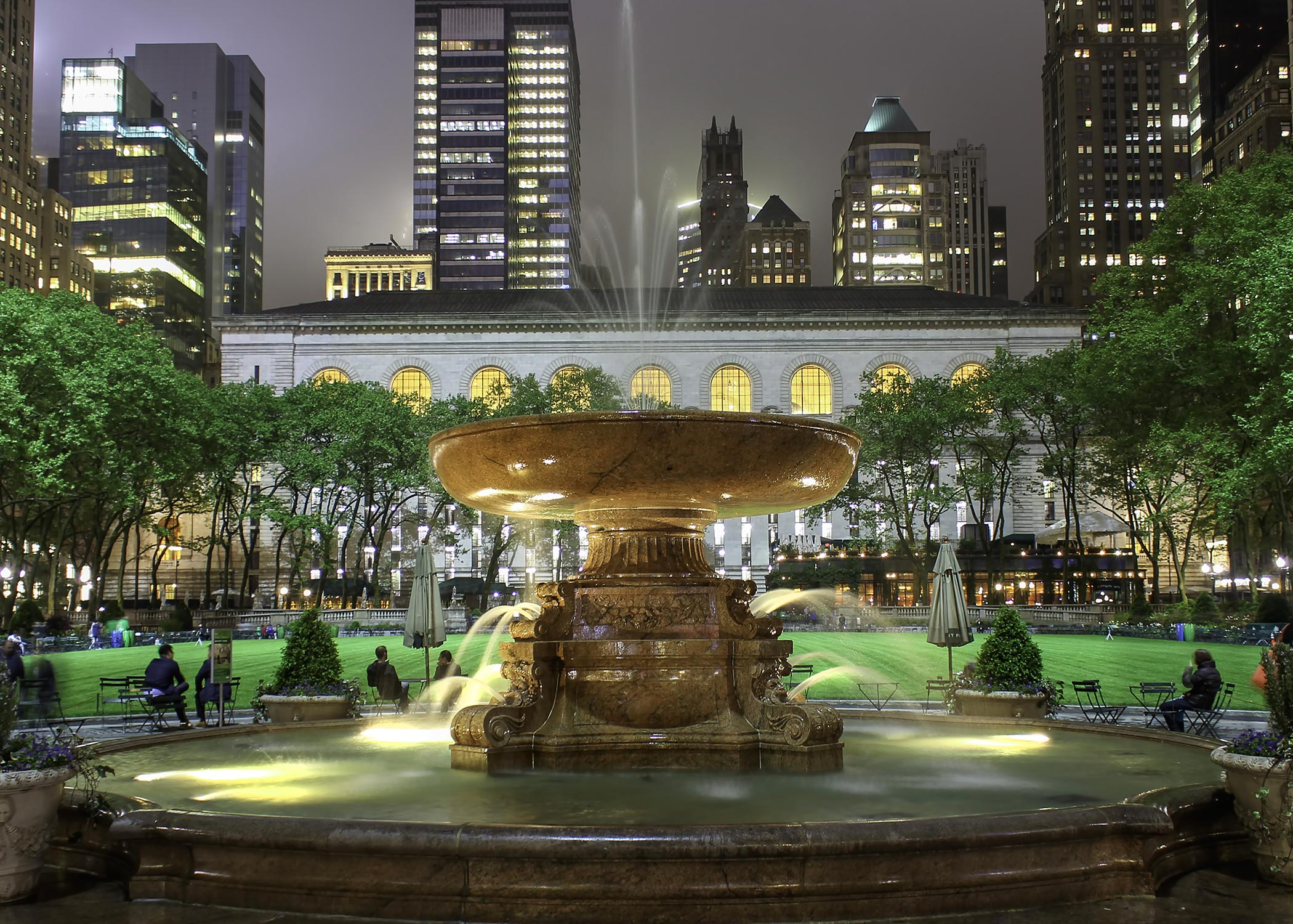 Night time photo of a large fountain in Bryant Park
