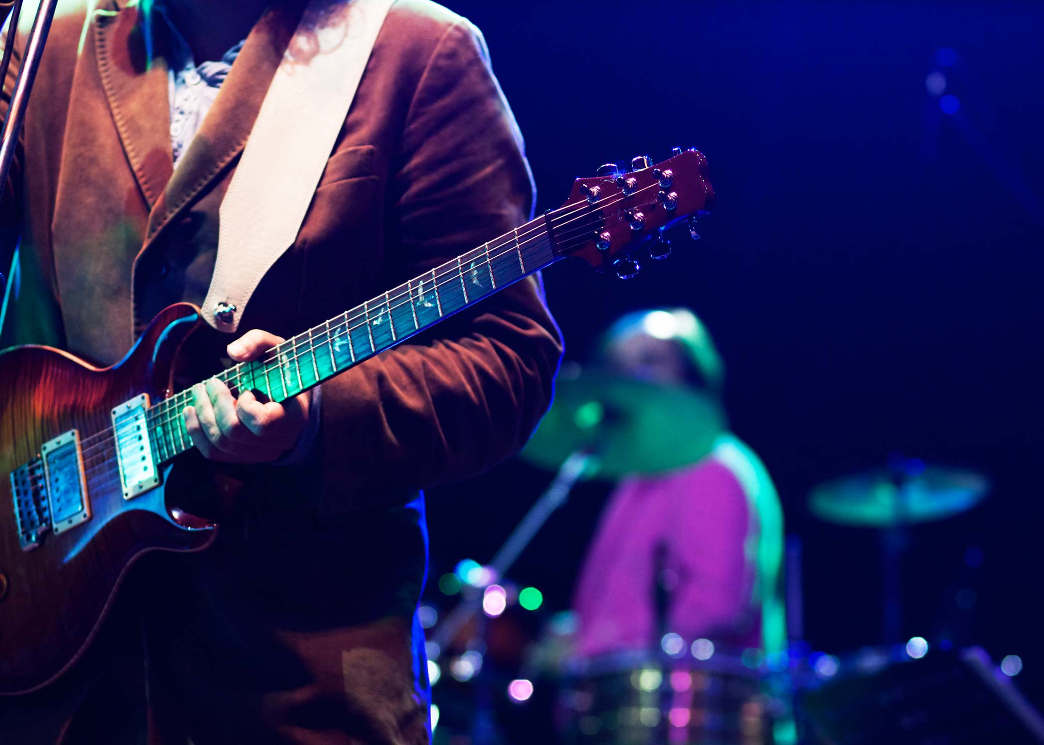 Musician holding a guitar with a drummer in the background