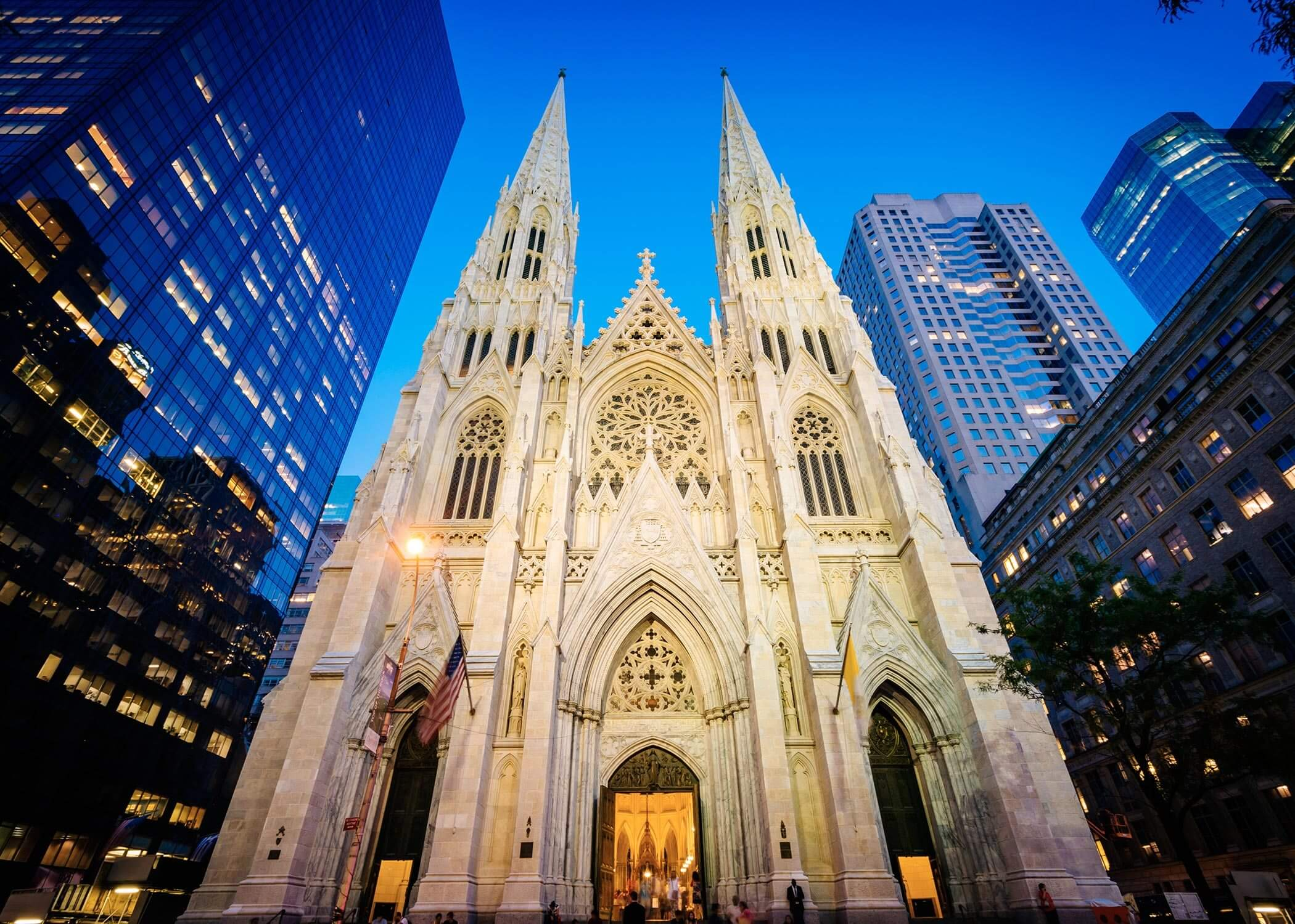 The exterior of a large white gothic cathedral against a blue evening sky surrounded by modern city buildings