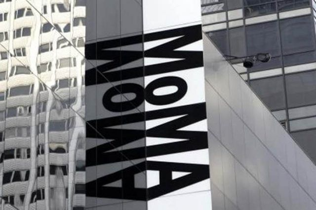 An outdoor shot of a building size with the letters MoMA in black reflecting on glass windows