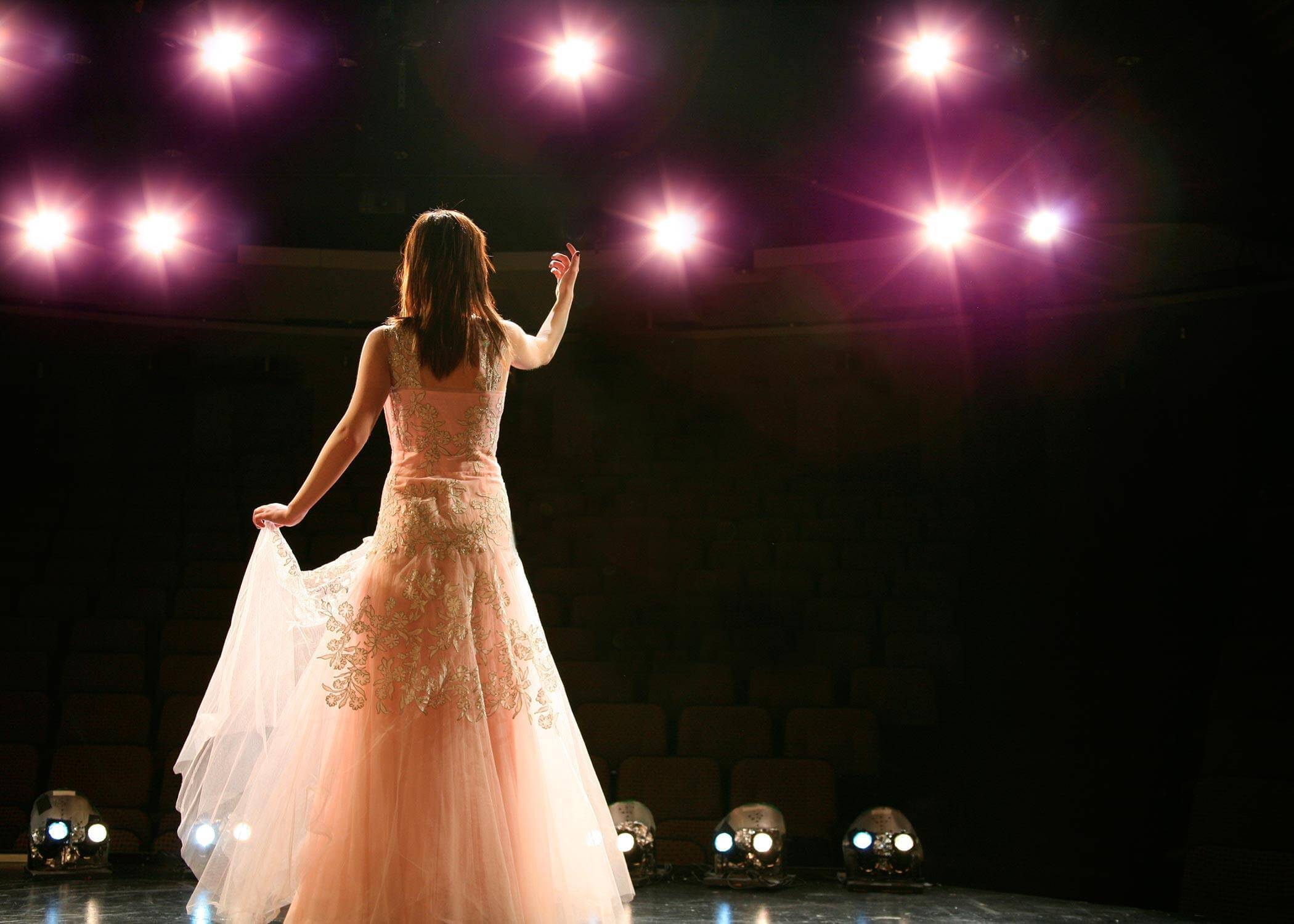 A woman on a stage in a white dress with one arm raised facing a darkened audience and pink stage lights