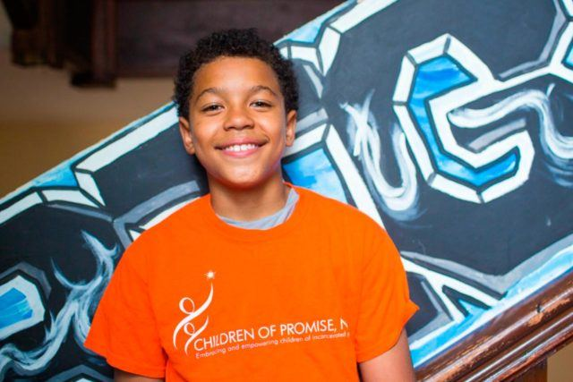 Smiling child wearing a Children of Promise t-shirt