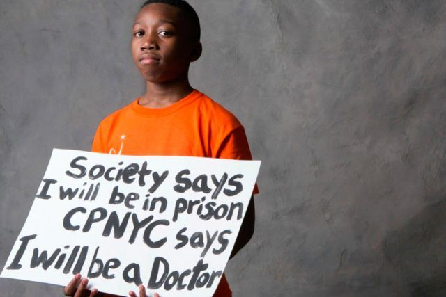 """Child holding a sign that says """"Society says I will be in prison CPNYC says I will be a Doctor"""""""