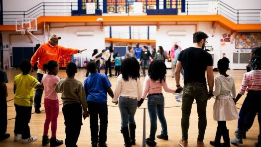 Gym with children and adults holding hands