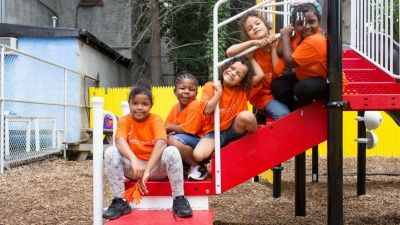five children sitting on stairs in a playground