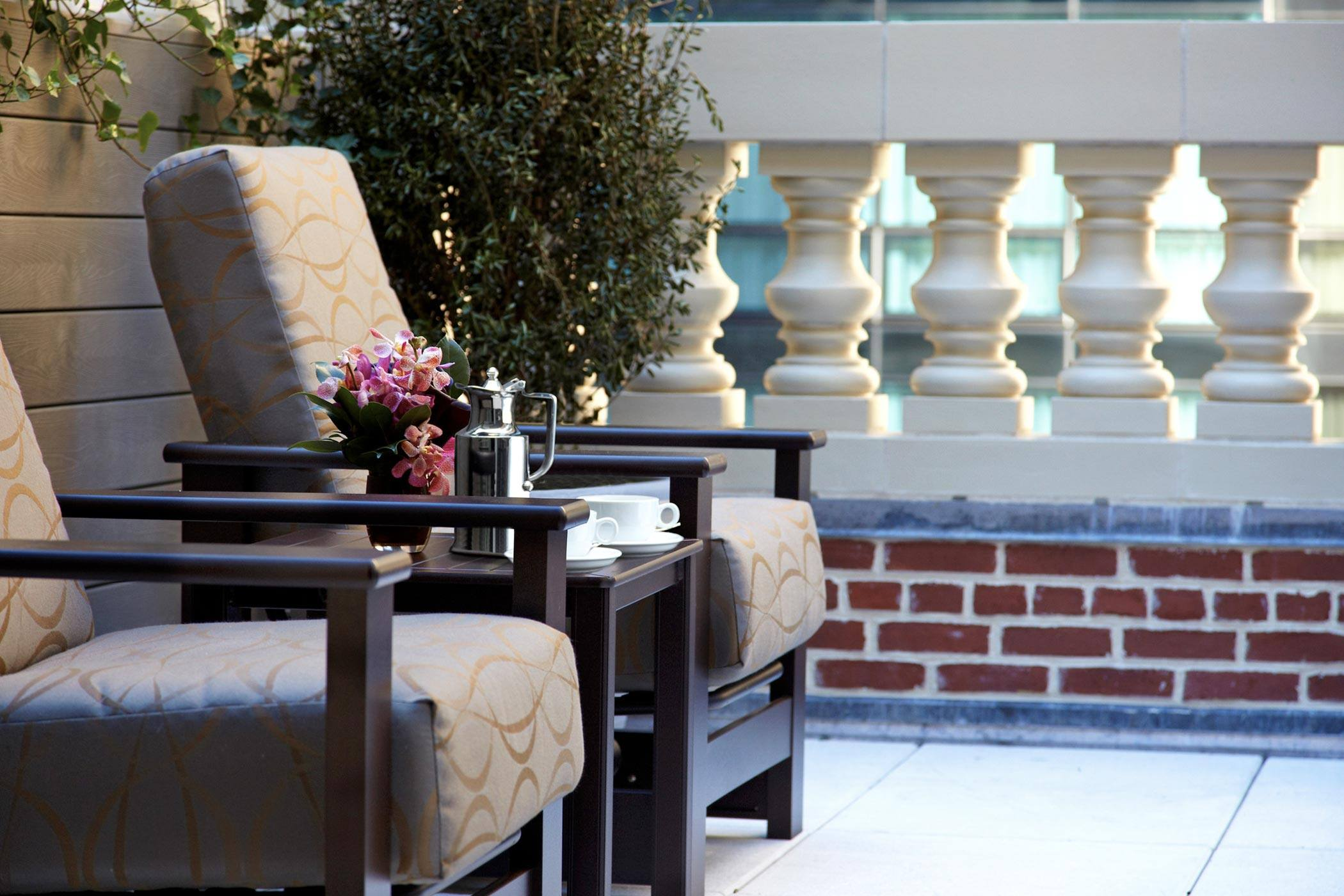 Two chairs on a terrace with flowers and cups