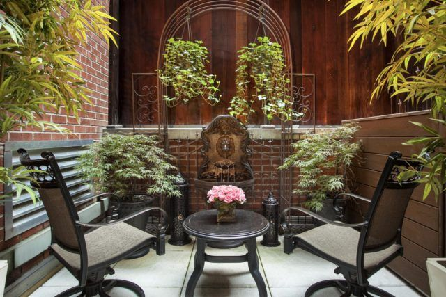 Outdoor terrace with two chairs and a small table surrounded by plants