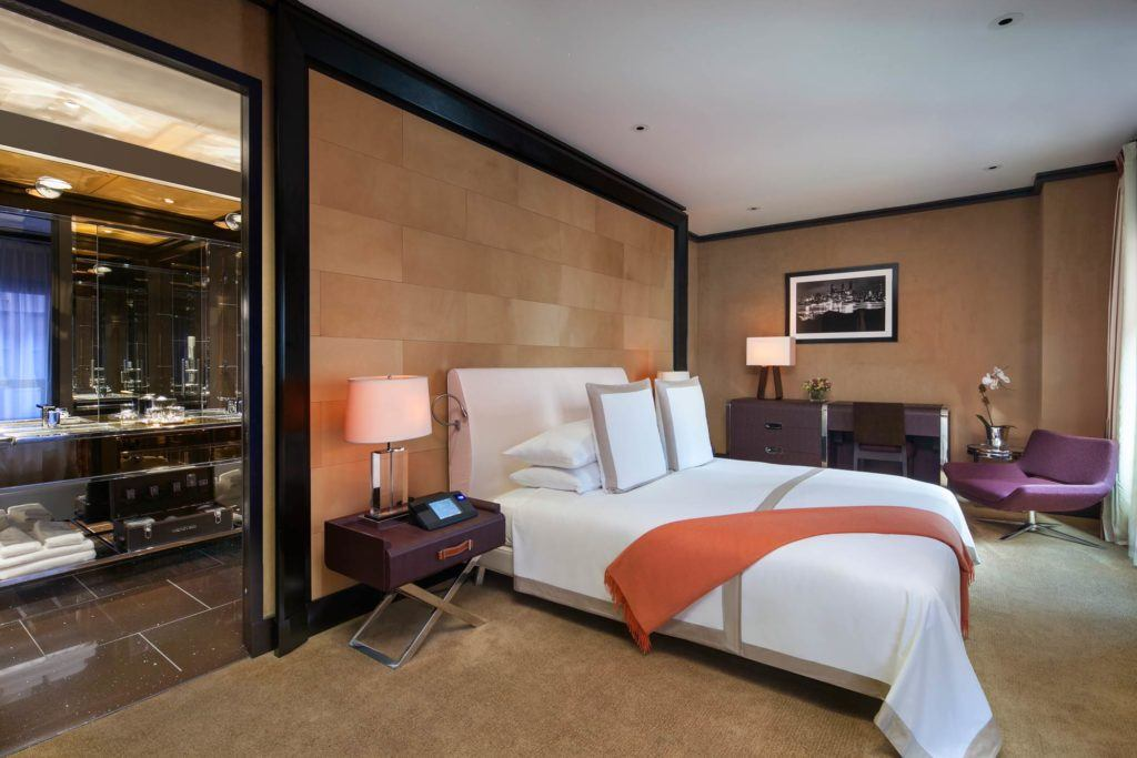 A suite bedroom with a King Size bed with an orange throw, and an entrance to a modern bathroom.