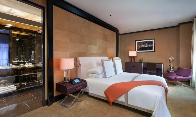 A suite bedroom with a King Size bed dressed in white sheets and an orange throw, and an entrance to a modern bathroom.