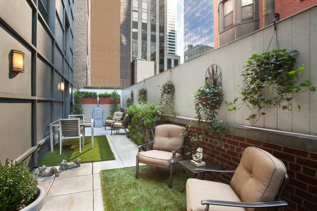Private outdoor terrace with seating, tables, many plants