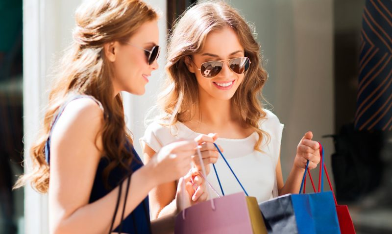 Two women with sun glasses and shopping bags