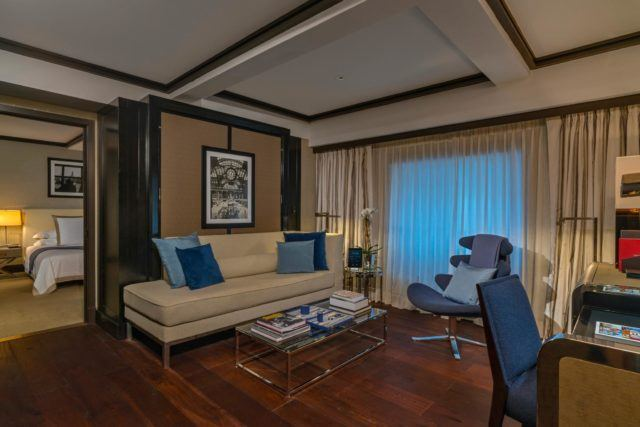 Suite living room with couch, chairs, coffee table and a desk