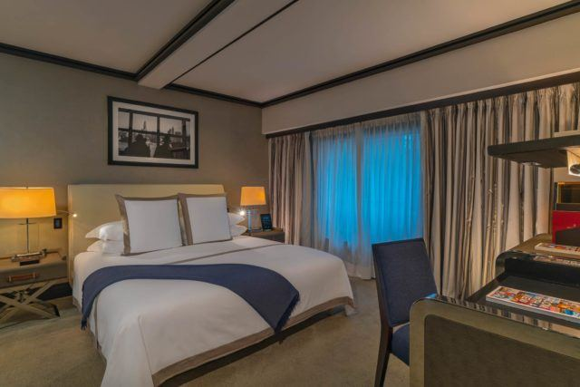 Room with medium grey walls and a king size bed with white dressings and a dark purple throw