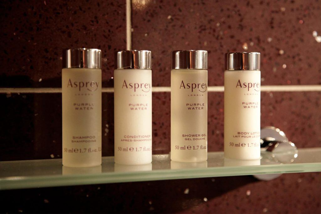 Four bottles of Asprey London products, Shampoo, Conditioner, Shower Gel, and Body Lotion