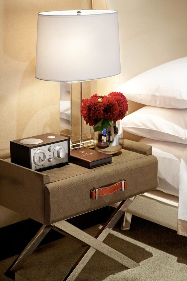 Night stand with flowers, lamp, notebook, and clock radio
