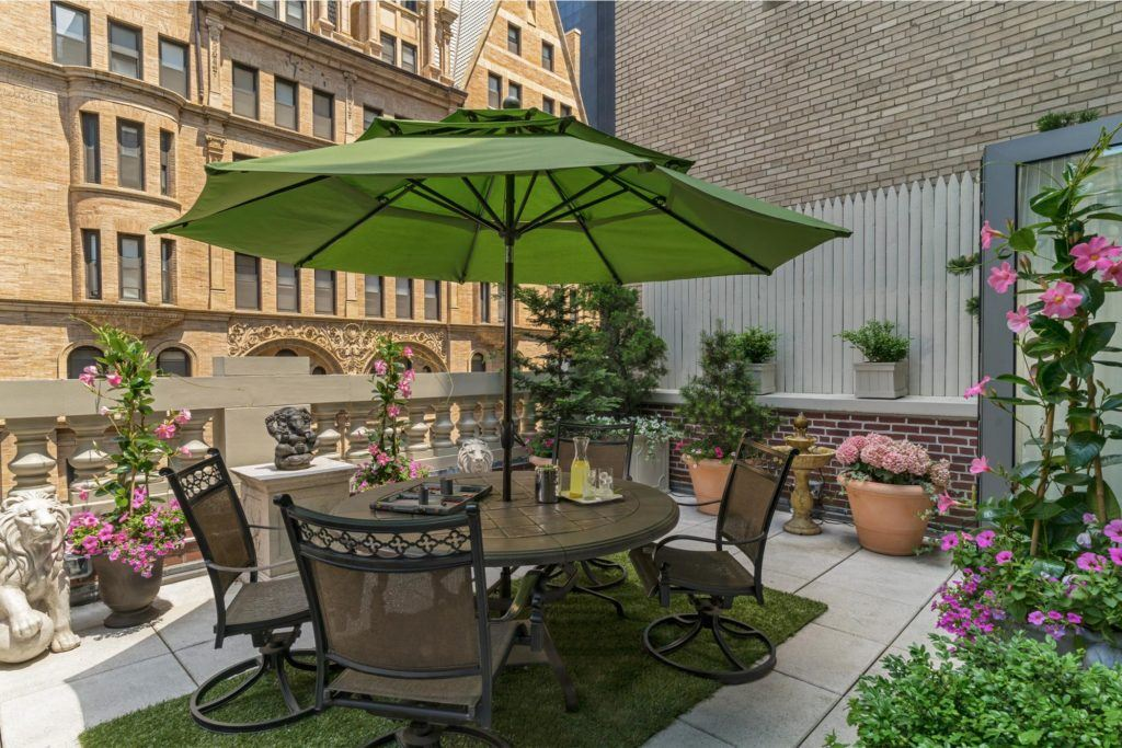 Outdoor terrace with round table, chairs, umbrella surrounded by plants