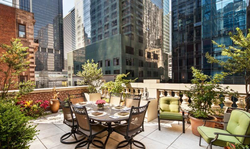 A large outdoor city terrace with a table and six chairs surrounded by large potted plants and comfy green chairs