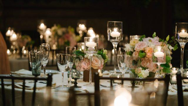 Wedding table setup with glasses, flowers and candles