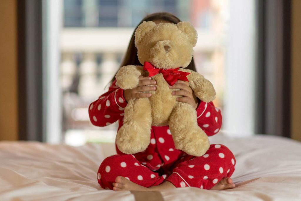 Girl sitting on a bed holding a teddy bear
