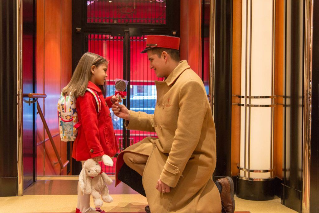 A concierge in a beige floor length coat and red hat bending down to give a little girl in a red coat a chocolate lollypop