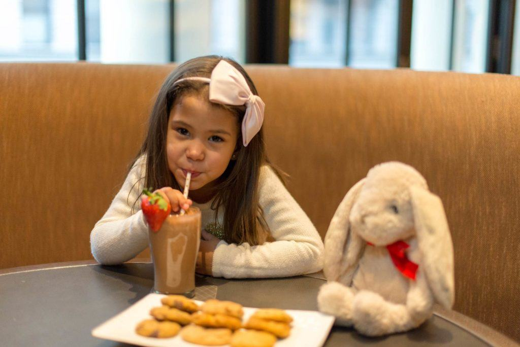 Girl sitting in booth drinking milk shake with plate of cookies and toy bunny