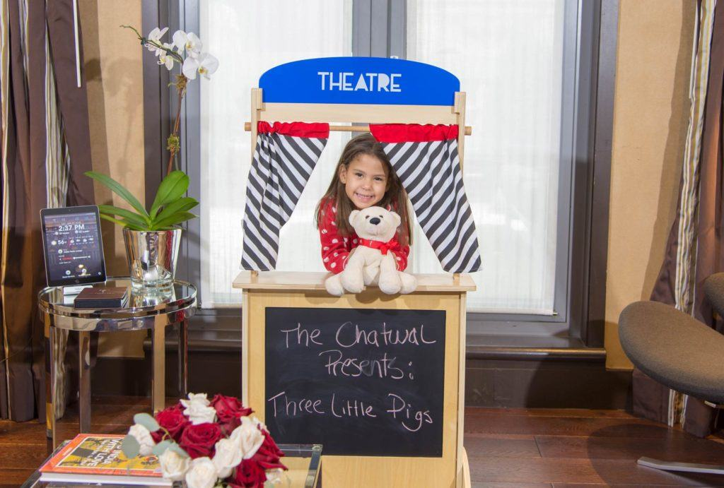 Girl performing puppet show with a teddy bear