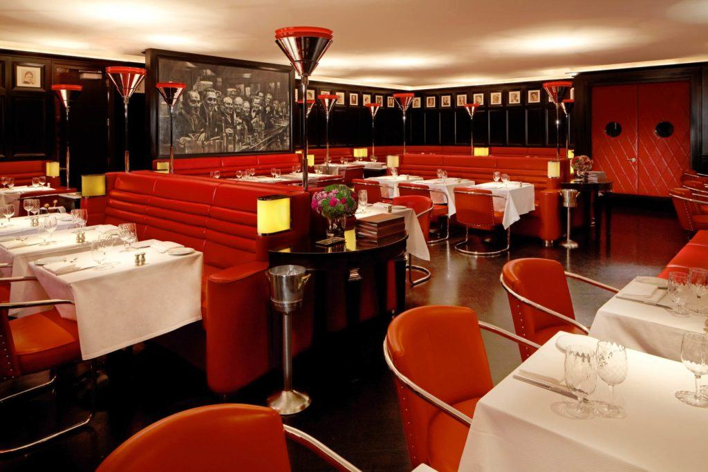 Dining room with red chairs and booths