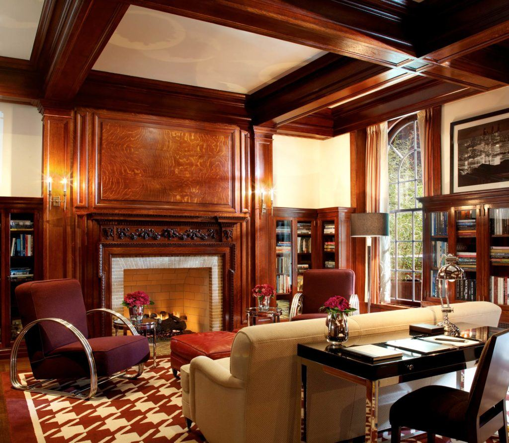 Wood panelled room with couch, chairs and fireplace