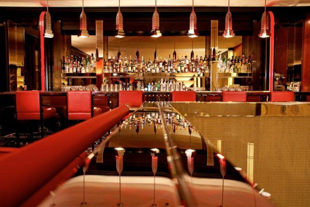 Hotel bar with red chairs and empire state building light fixtures