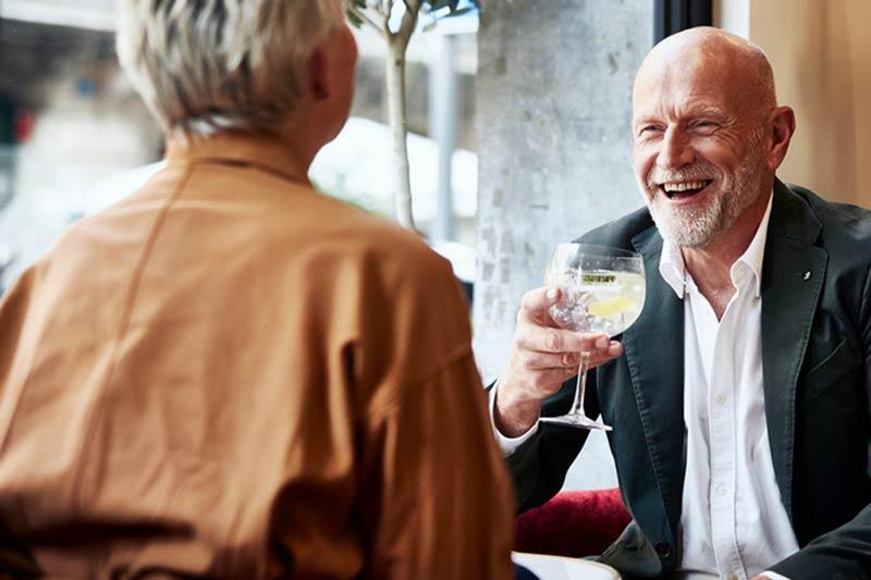 Happy senior man enjoying drinks while looking at woman in restaurant