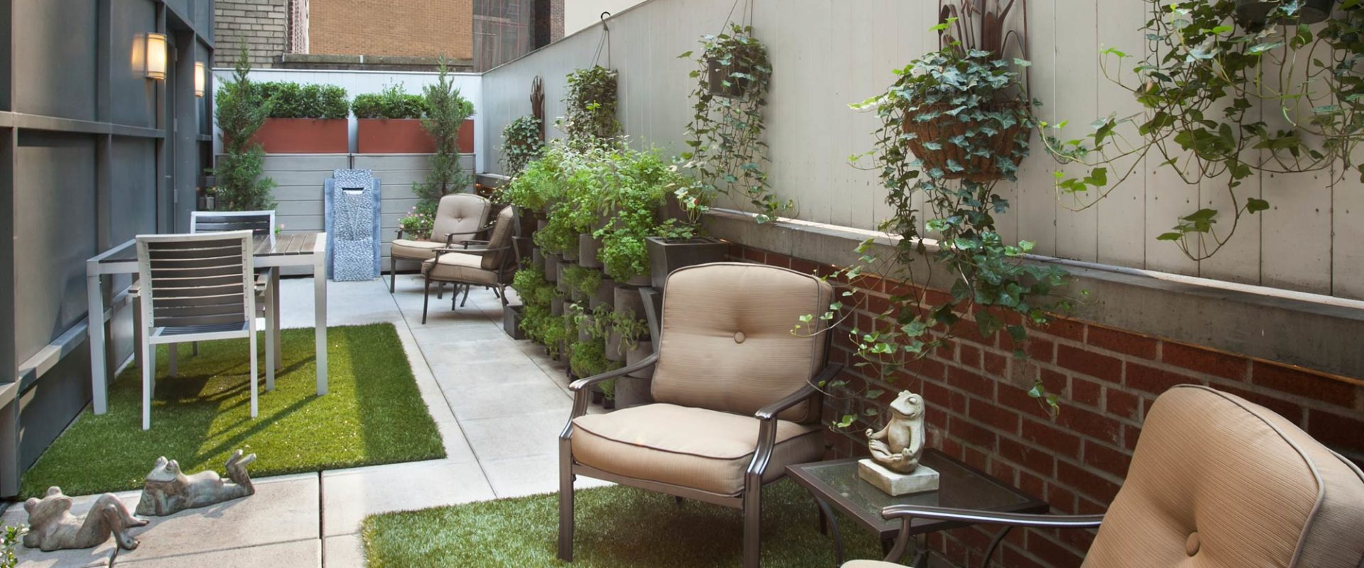 An enclosed outdoor city terrace with patio stones, a table and two chairs on green grass
