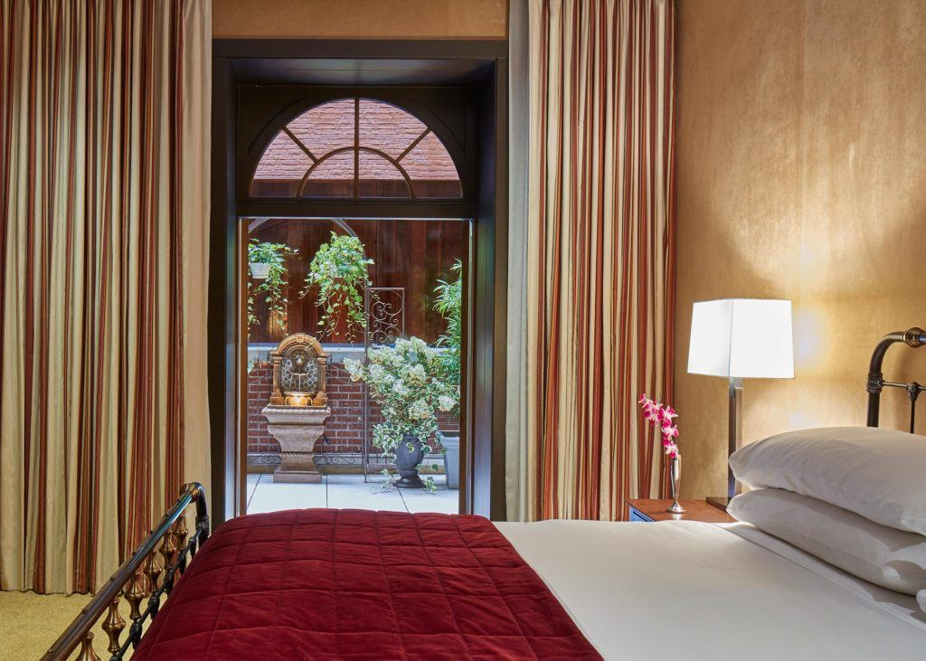 luxurious hotel suite bedroom with golden walls and carpet. curtained glass door looks out on to outdoor terrace with plants
