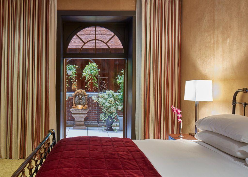 luxurious hotel suite bedroom with golden walls and door opened to outdoor terrace with plants