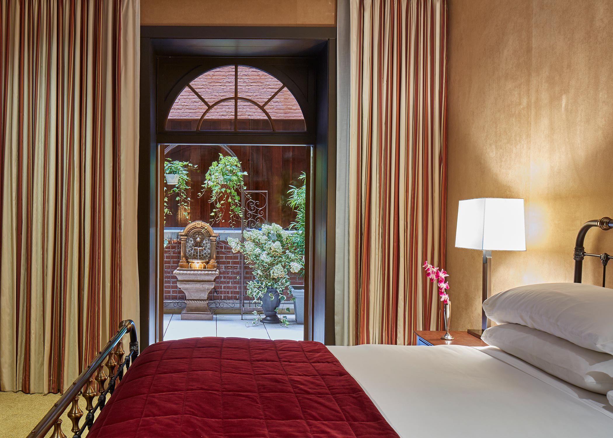 luxurious hotel suite bedroom with golden walls and door opened to outdoor terrace with plants