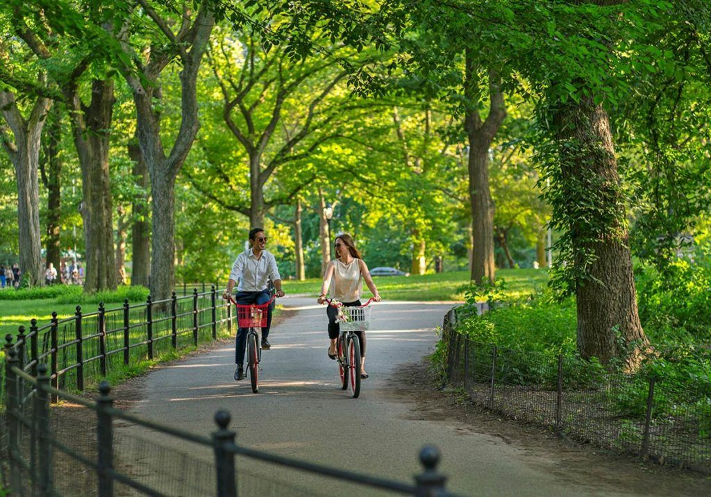 Couple riding bikes through Central Park