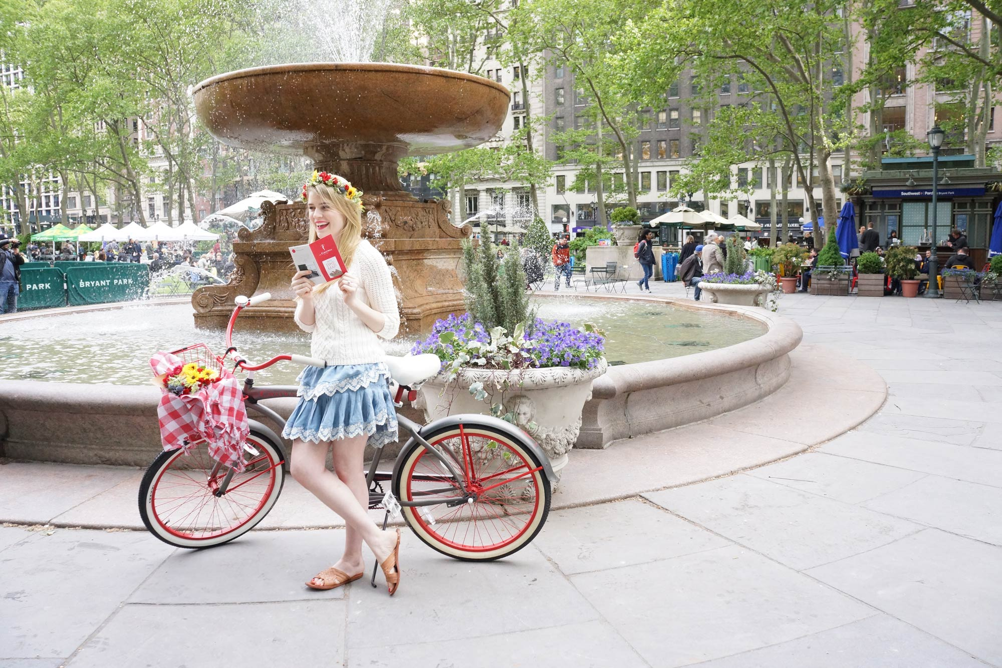 Woman with a flower crown and a vintage bicycle reading a pamphlet in front of a large fountain