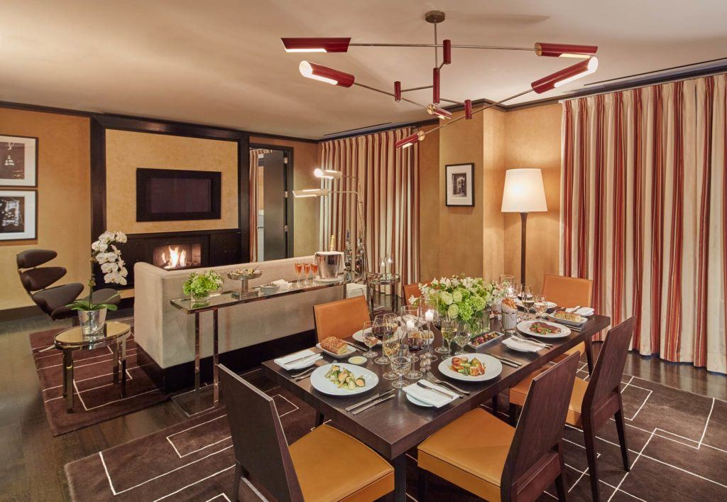 Suite with fireplace, couch, chair, and table with dinner served