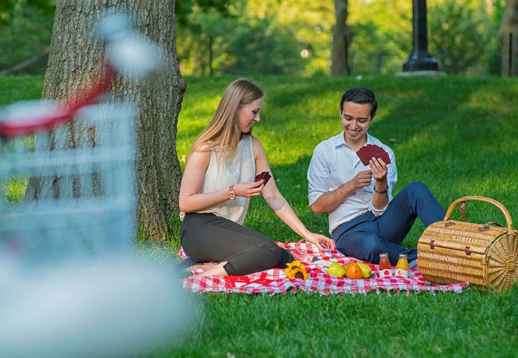 Couple playing cards in the park with a picnic setup