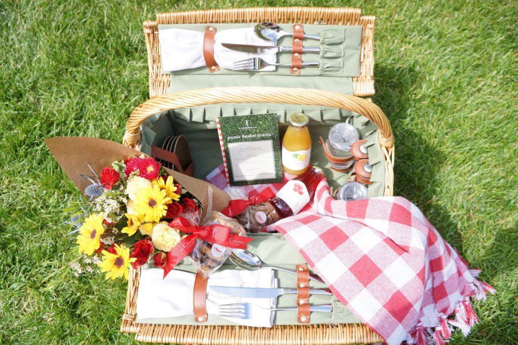 Picnic basket with juice, flowers, cookies, cutlery and menu