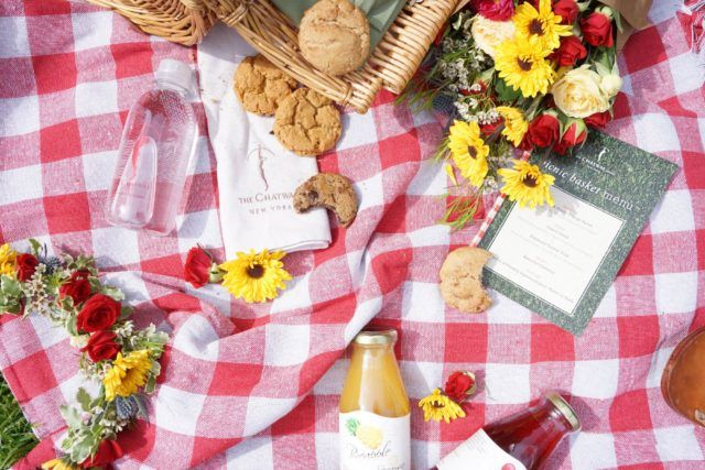 Picnic blanket with flowers, cookies, juice and picnic menu