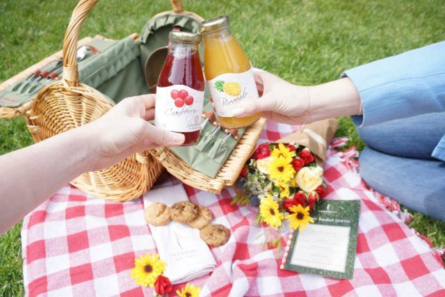 Picnic blanket with basket, flowers, cookies, picnic menu and people toasting with juice